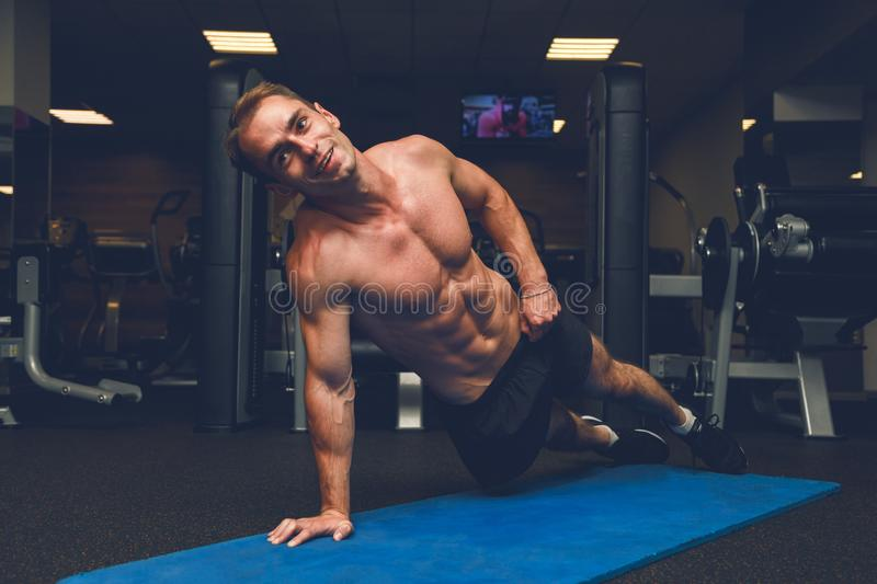 Handsome shirtless muscular male doing push-ups on the floor at gym. Handsome shirtless muscular male doing push-ups on the floor royalty free stock photography