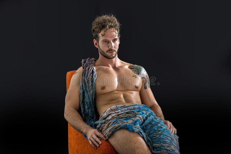 Handsome shirtless muscular man in briefs. Covering with long elegant scarf, sitting, isolated on black background in studio shot royalty free stock image
