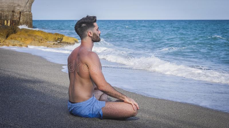 Young Man Meditating or Doing Yoga Exercise by Sea royalty free stock photo