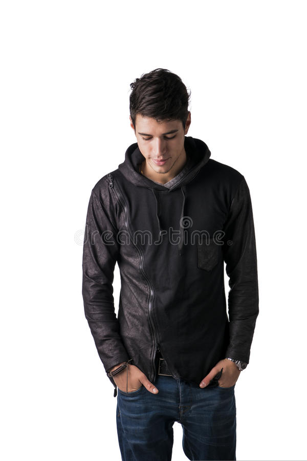 Handsome shy young man in black hoodie sweater standing royalty free stock image