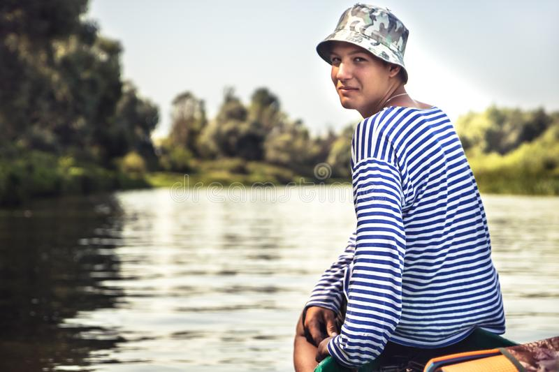 Handsome simple teenager boy traveling by boat on river during countryside summer camp holidays stock photos