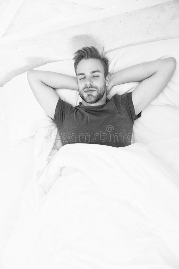 Handsome and sleepy. Sexy man sleeping in bed. Relaxing man in bedroom. Attractive single man being calm and relaxed stock image