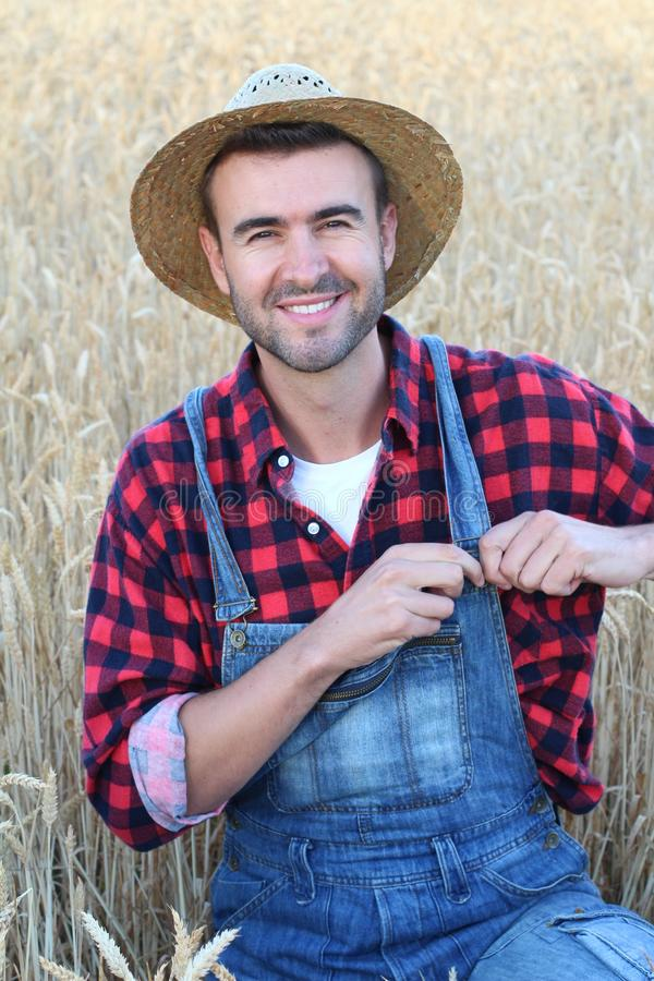 Handsome smiley farmer standing in a wheat field fixing his overalls royalty free stock photo