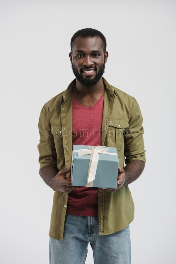 handsome smiling african american man holding present box stock image