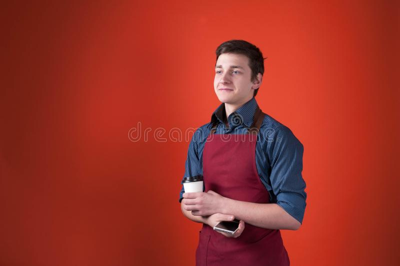 Handsome smiling barista with dark hair in burgundy apron holding paper cup and smartphone. On orange background with copy space royalty free stock image