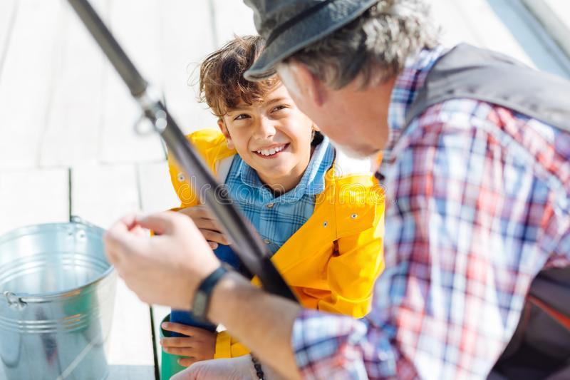 Handsome smiling dark-eyed boy fishing with grandfather stock photography