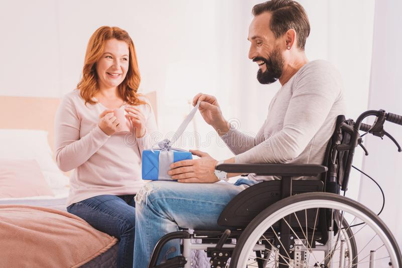 Handsome smiling disabled man opening his birthday present. What is here. Cheerful bearded men opening a present while his wife sitting nearby stock photos