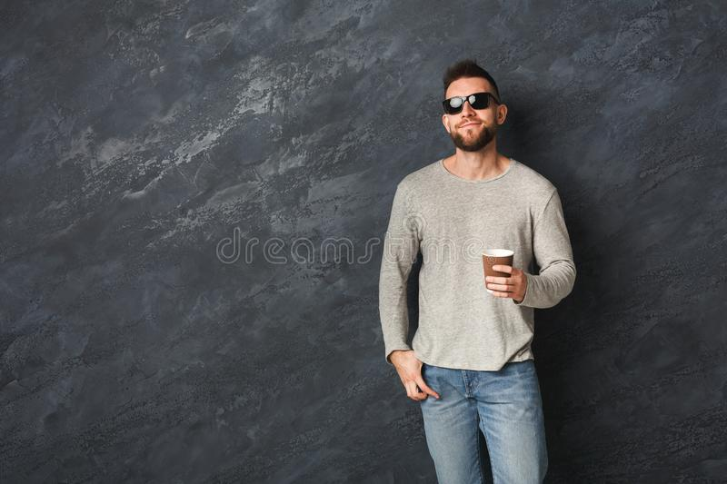 Handsome smiling man with coffee in studio stock image