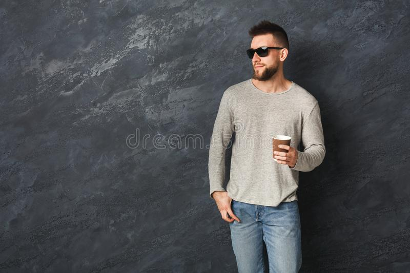 Handsome smiling man with coffee in studio royalty free stock photography
