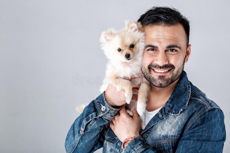 Man holds pomeranian dog. Handsome smiling man in denim jacket holds pomeranian dog. Spitz. people and pets royalty free stock photos