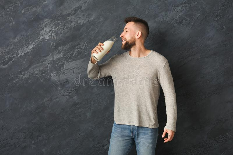 Handsome smiling man drinking milk from bottle in studio royalty free stock photos