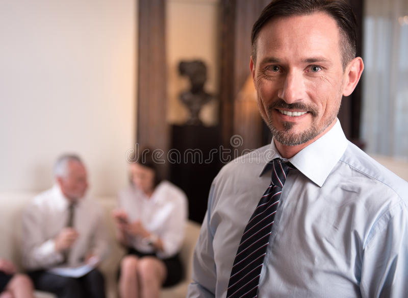 Handsome smiling man expressing gladness. Epitome of manhood. Pleasant delighted handsome men smiling and expressing gladness while his colleagues sitting on the stock photos