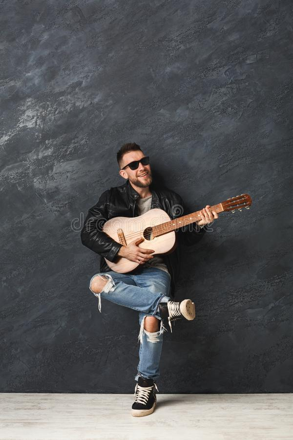 Handsome smiling man with guitar posing in studio stock photos