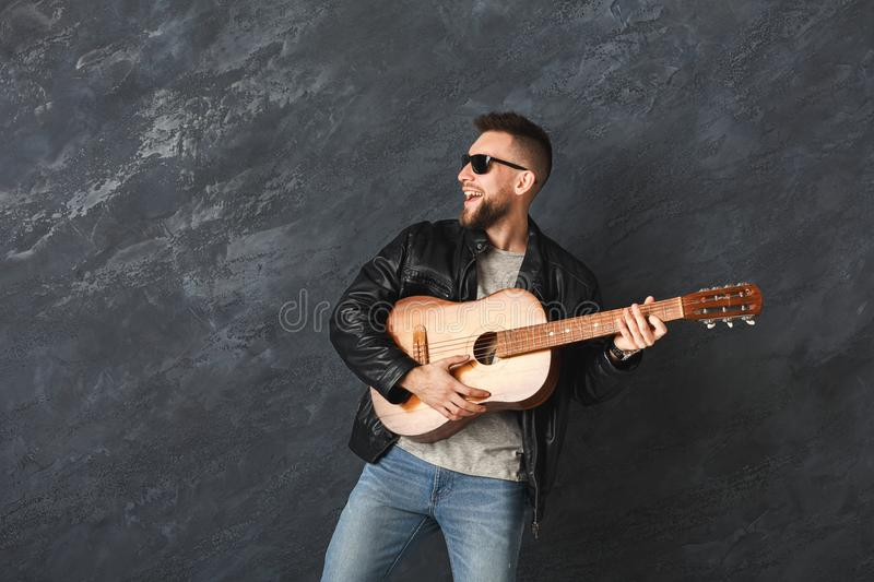 Handsome smiling man with guitar posing in studio royalty free stock photography