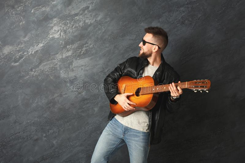 Handsome smiling man with guitar posing in studio stock images