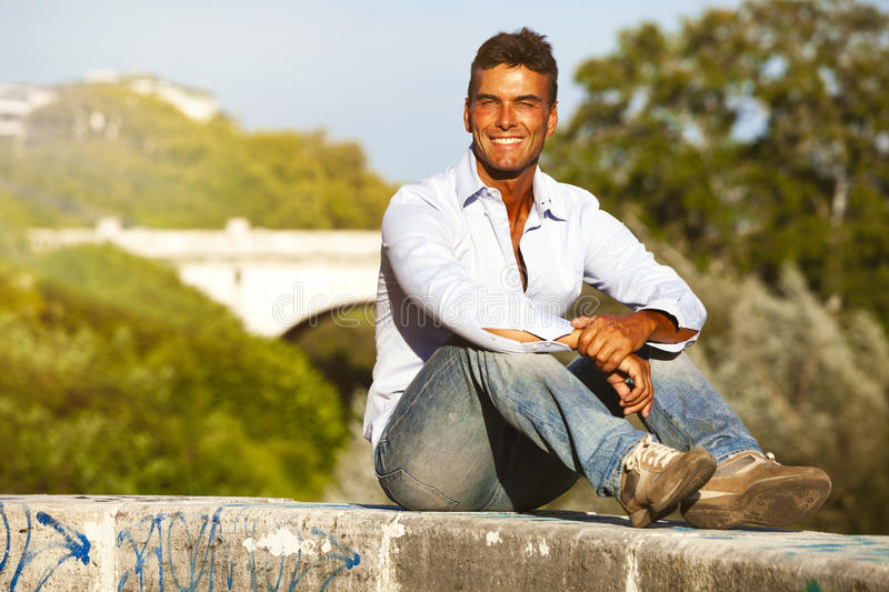 Handsome smiling man Italian model outdoors, sitting on the wall royalty free stock image