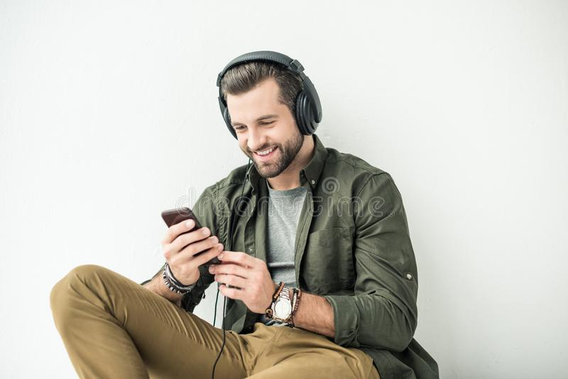 handsome smiling man listening music with smartphone royalty free stock photo