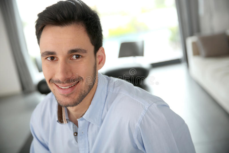 Handsome smiling man in living-room stock photography
