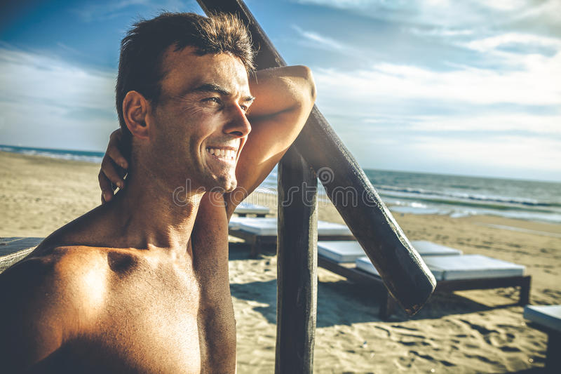 Handsome smiling man outdoor on the beach at the sea royalty free stock photography