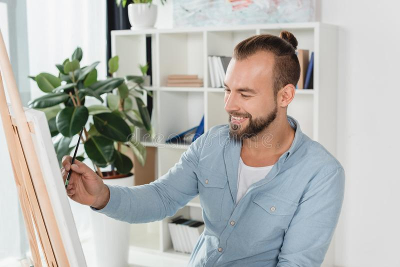 Man painting on canvas. Handsome smiling man painting on canvas with oil paint stock photos