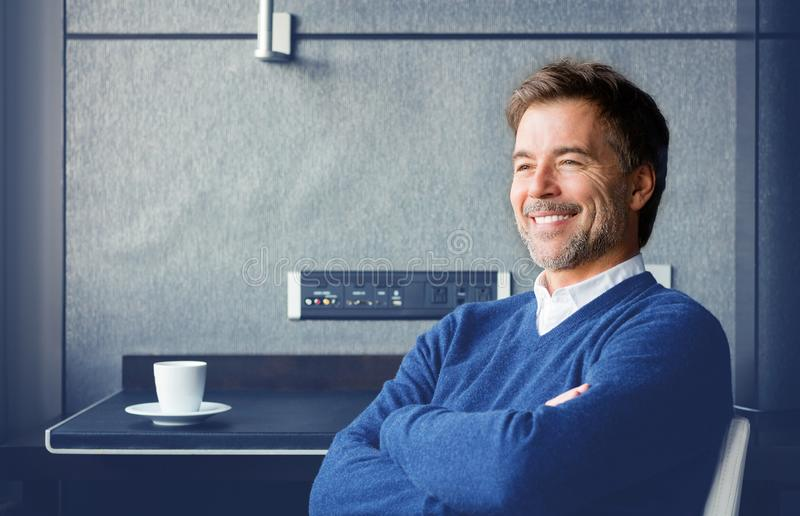 Handsome smiling man sitting at the desk relaxing. Arms crossed he is looking away stock image