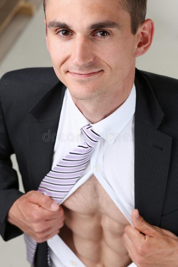 Handsome smiling man in tie rip clothes off torso showing abs. stock photography