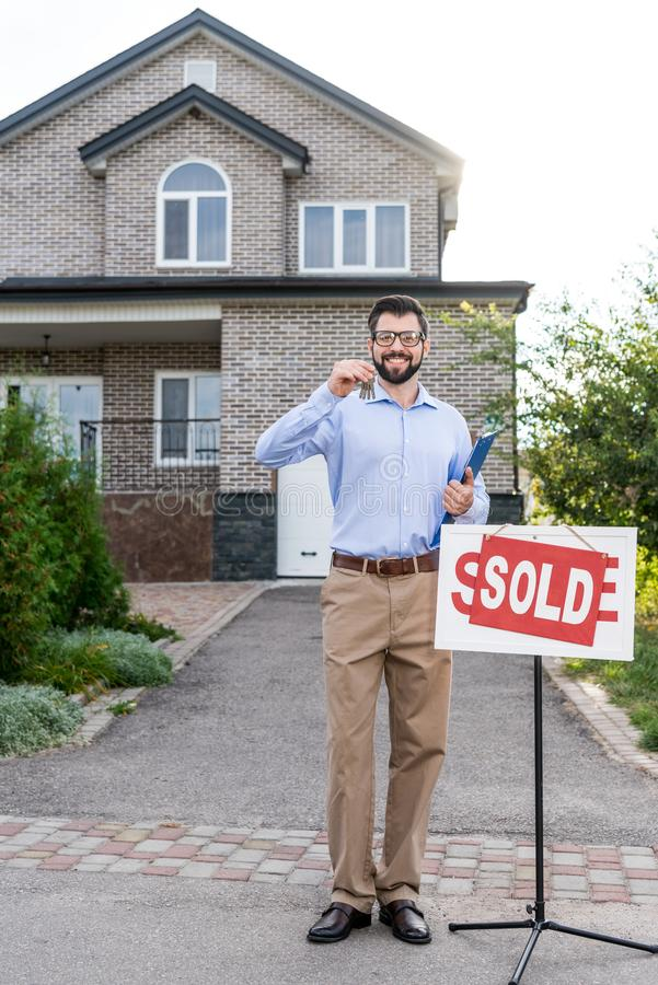 handsome smiling realtor with keys of royalty free stock photography