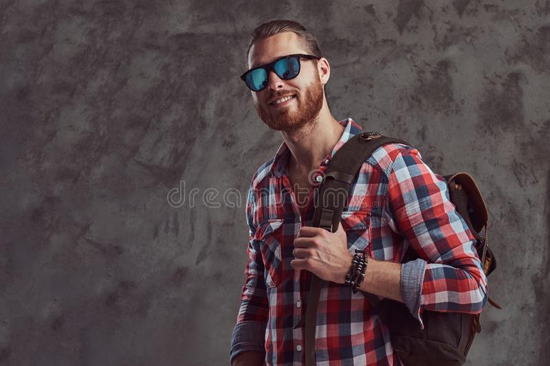 Handsome stylish redhead traveler in a flannel shirt and sunglasses with a backpack, posing in a studio on a gray stock photo