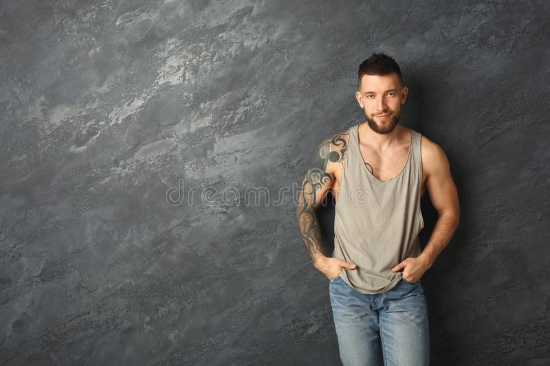 Handsome smiling tattooed man posing in studio stock photography