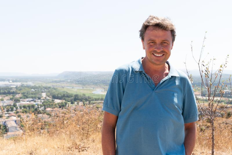 Handsome smiling tourist man in cavaillon hill town with panoramic view city background in south France summer day stock image