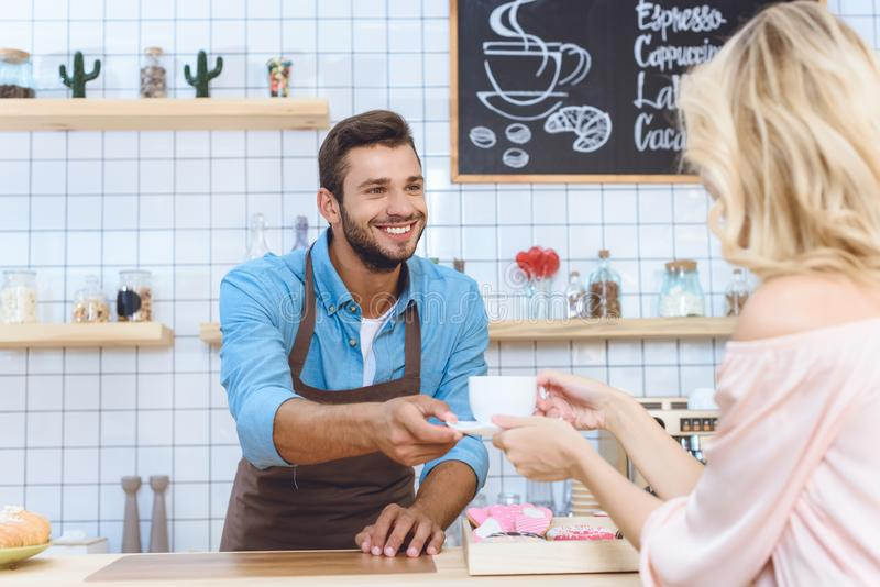Handsome smiling young barista giving coffee to client. In cafe royalty free stock images