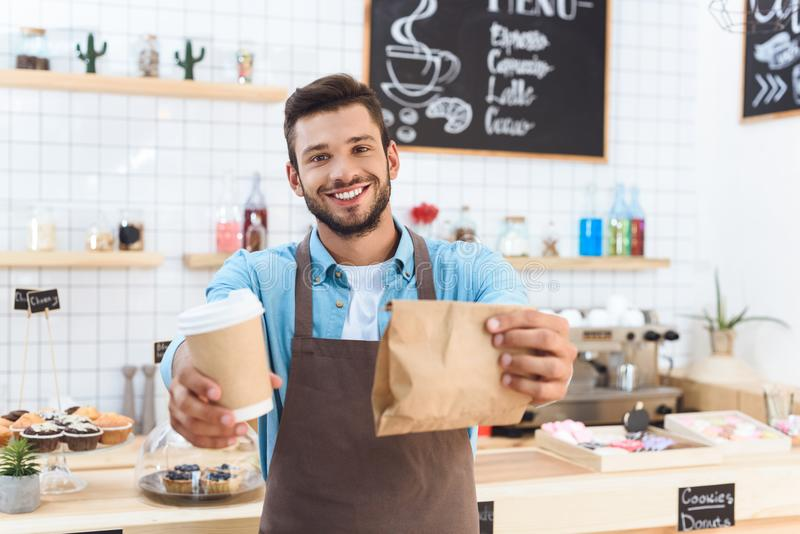 Handsome smiling young barista holding coffee to go in paper cup and take away food. In paper bag royalty free stock images