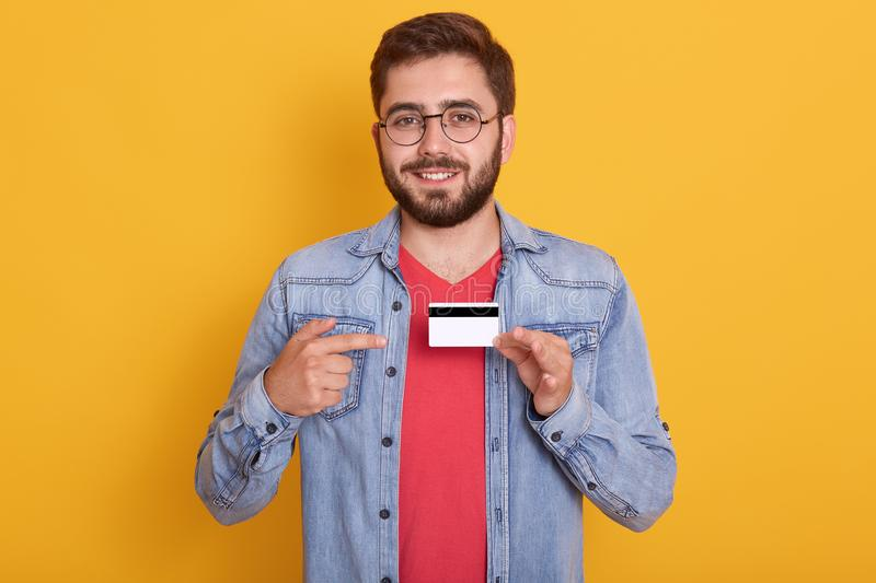 Handsome smiling young man with bead wearing glasses, red t shirt and denim jacket showing credit card, pointing on it with fore royalty free stock photography