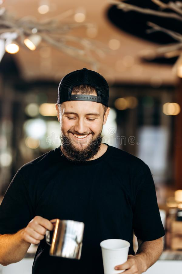 A handsome smiling young man with beard,dressed in casual style,adds milk to the coffee in a modern coffee shop. stock photography