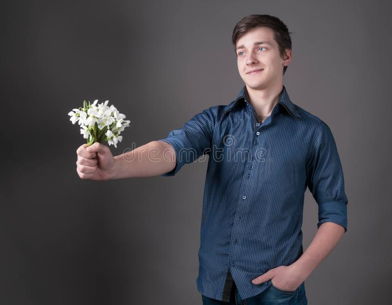 Handsome smiling young man in blue shirt holding in outstretched hand bouquet with white snowdrops royalty free stock photography