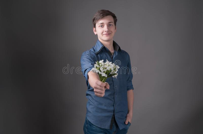 Handsome smiling young man in blue shirt holding in outstretched hand bouquet with white snowdrops and looking at camera. On grey background with copy space royalty free stock photography