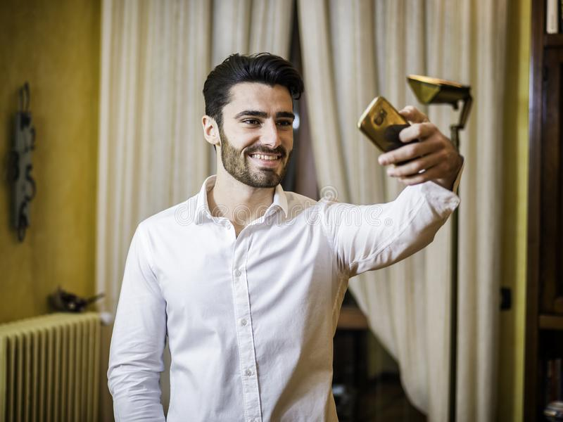 Handsome young man doing selfie at home royalty free stock images