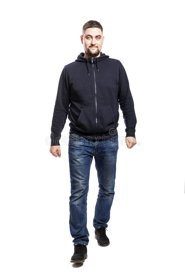 A handsome smiling young man in a hoodie and jeans is walking forward and looking at the camera. Full height. Isolated over white royalty free stock photos