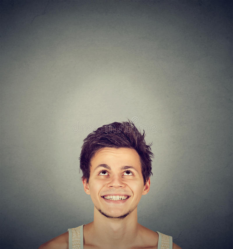 Handsome smiling young man looking up stock photography
