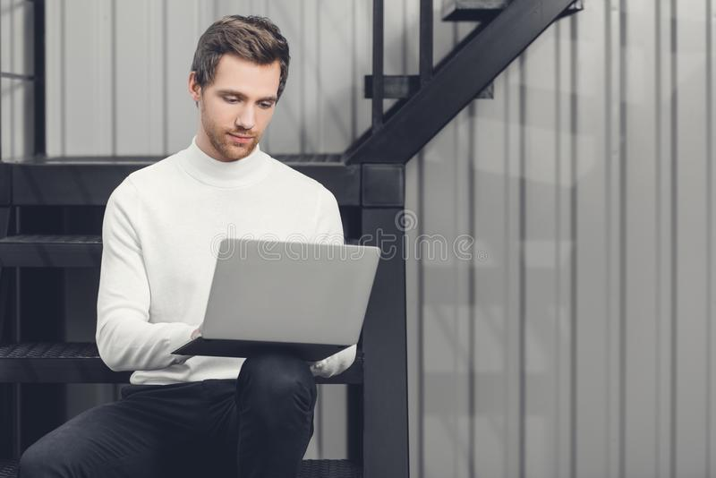 Handsome smiling young man sitting on stairs and using laptop royalty free stock photo
