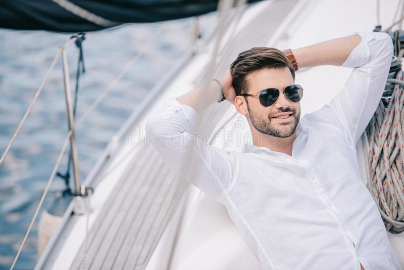 handsome smiling young man in sunglasses resting with hands behind head royalty free stock photos