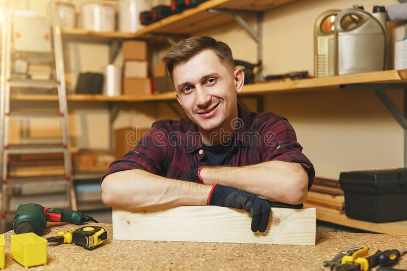 Handsome smiling young man working in carpentry workshop at wooden table place with piece of wood stock photos