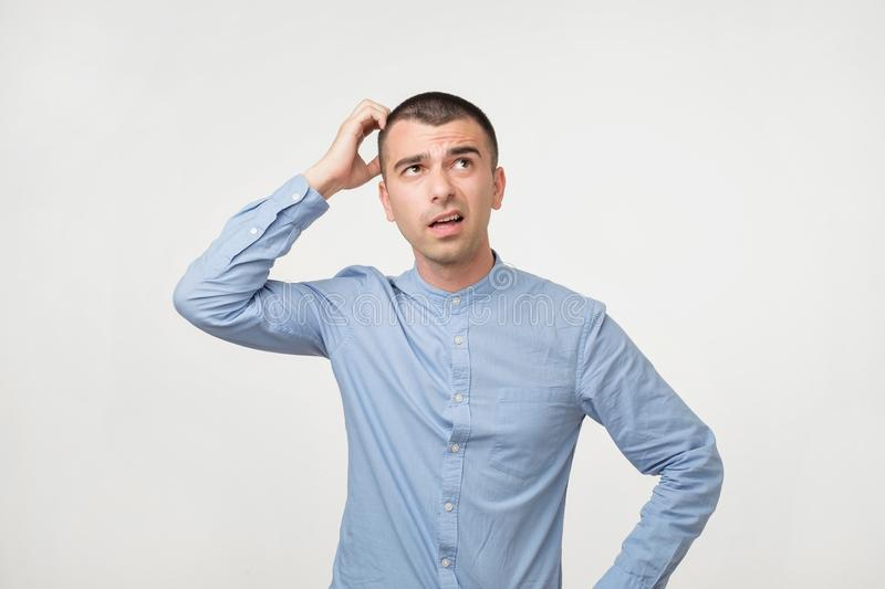 Handsome spanish guy in blue shirt, frowning and looking unsatisfied while scratching head royalty free stock photo