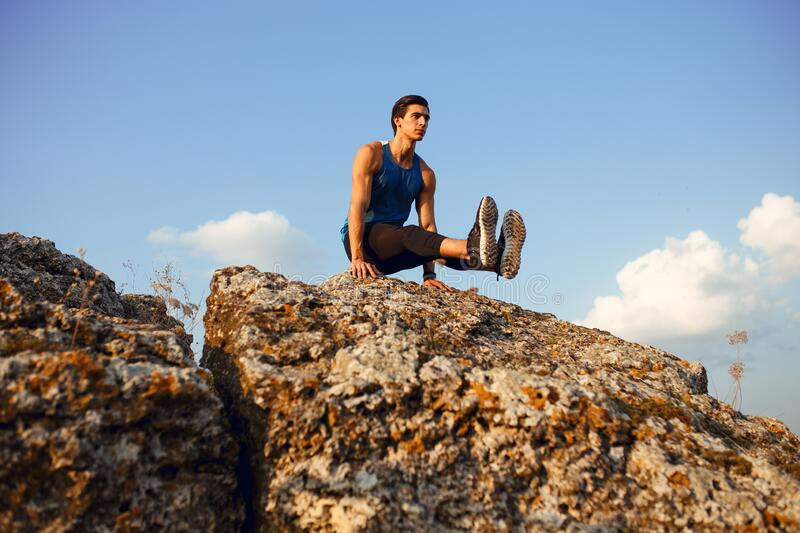 Handsome sportive young man doing stretching exercises on roch, before workout outside on forest, mountain background. stock photos