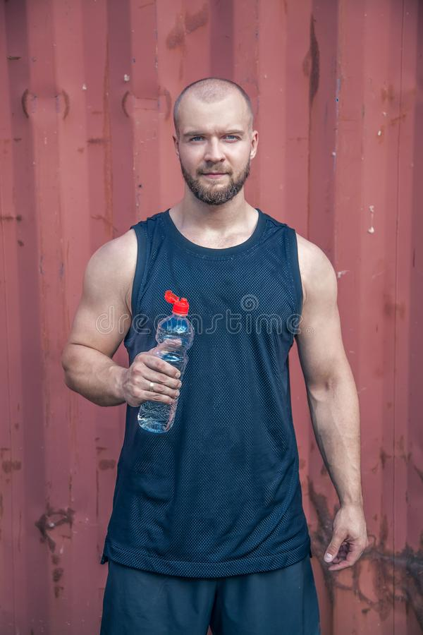 Handsome sportsman is hold bottle of water. He is standing against urban background. dressed in sports clothes stock photo