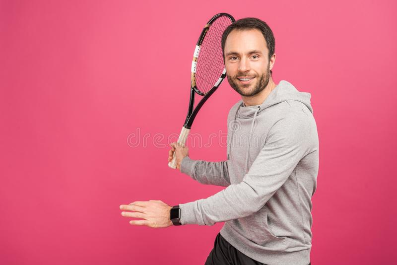 Handsome sportsman playing tennis with racket, isolated. On pink royalty free stock photos