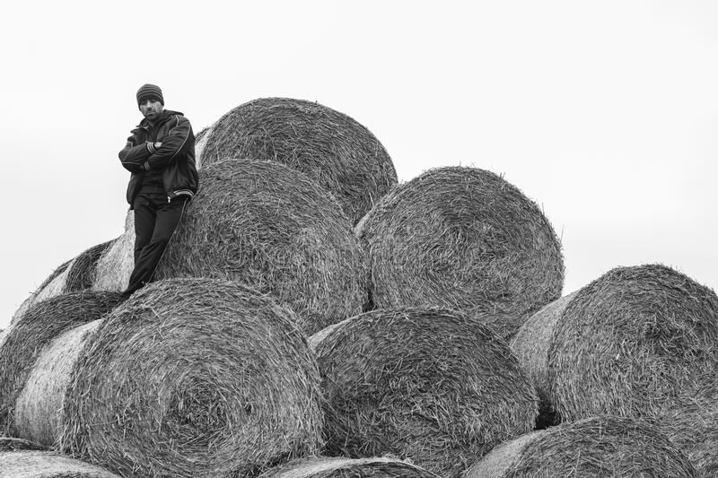 Handsome sportsman is resting on a haystack royalty free stock photos