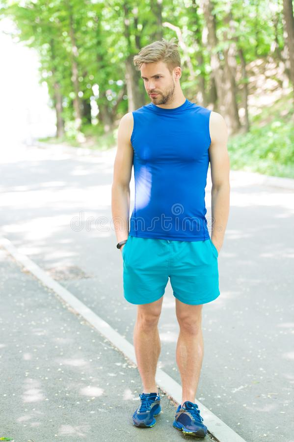 Handsome sportsman in sportswear outdoors. Active sportsman training outdoor. Sportsman living healthy lifestyle. Workout in park. Daily walk for healthy life stock image