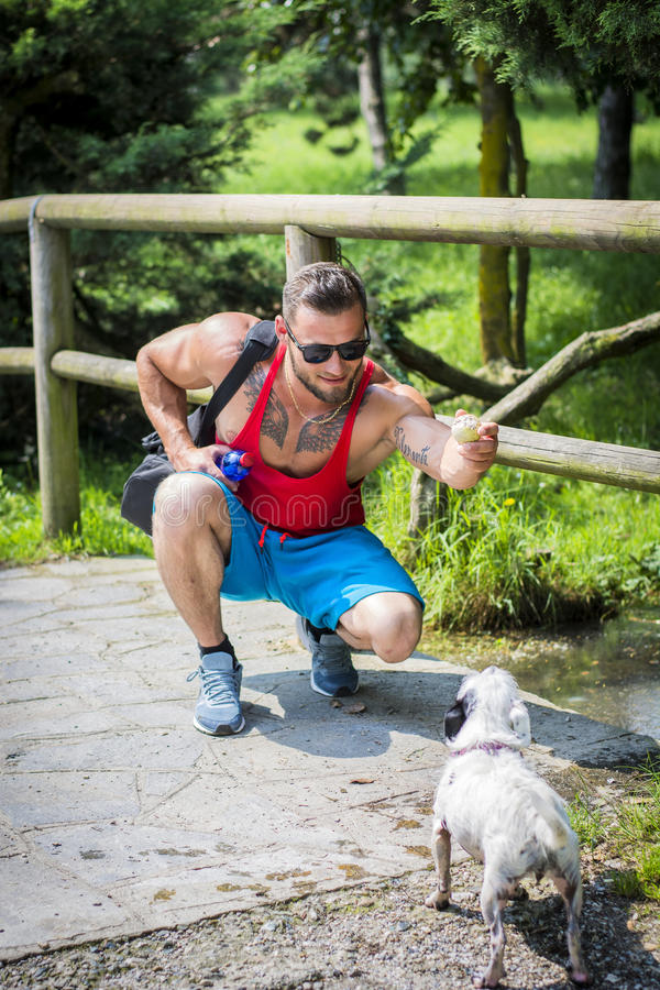 Handsome sportsman in sunglasses playing with pet outdoor stock photo