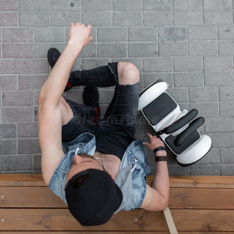 Handsome sporty young man sitting on a wooden step next to a modern white hoverboard. Top view on fashionable guy. In stylish clothes in a black cap. Healthy stock images
